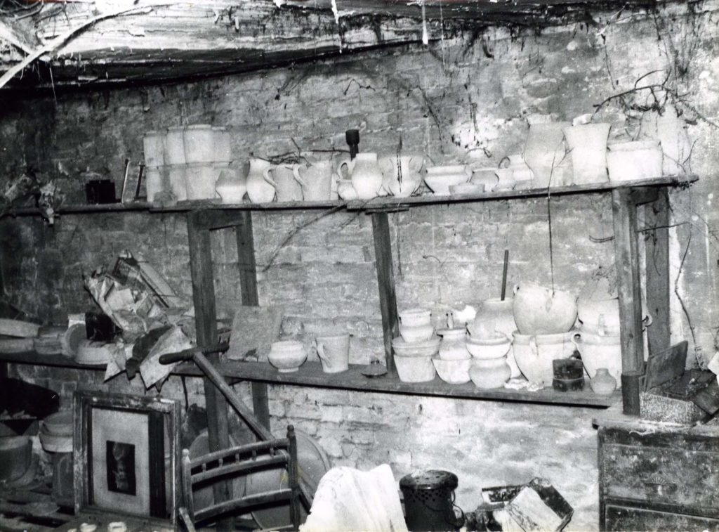a black and white photo showing shelves stacked with old pots and things