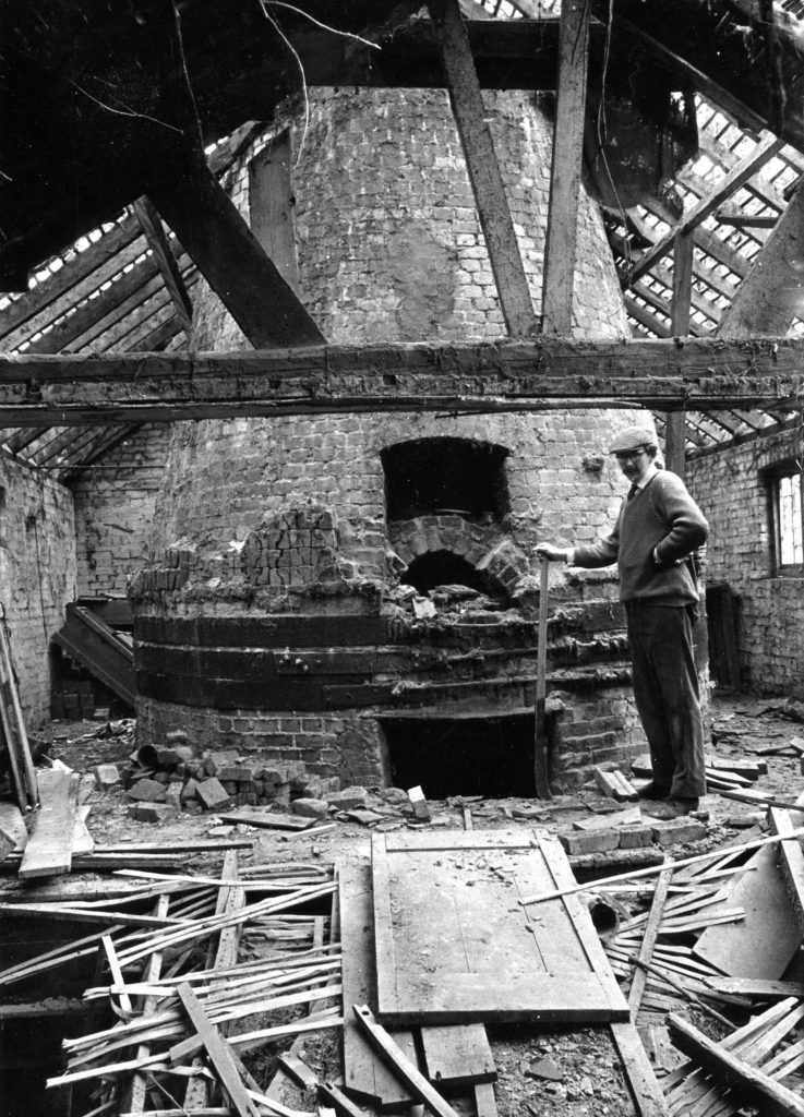 a photo of a man with shovel next to a brick kiln