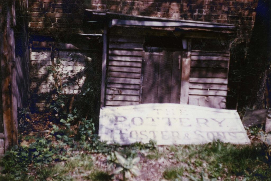 a colour photo of a an old sign saying Pottery Foster and Sons leaning against a derelict building