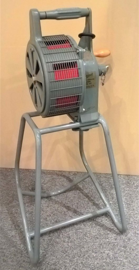 a photo of a grey cylindrical siren on grey legs