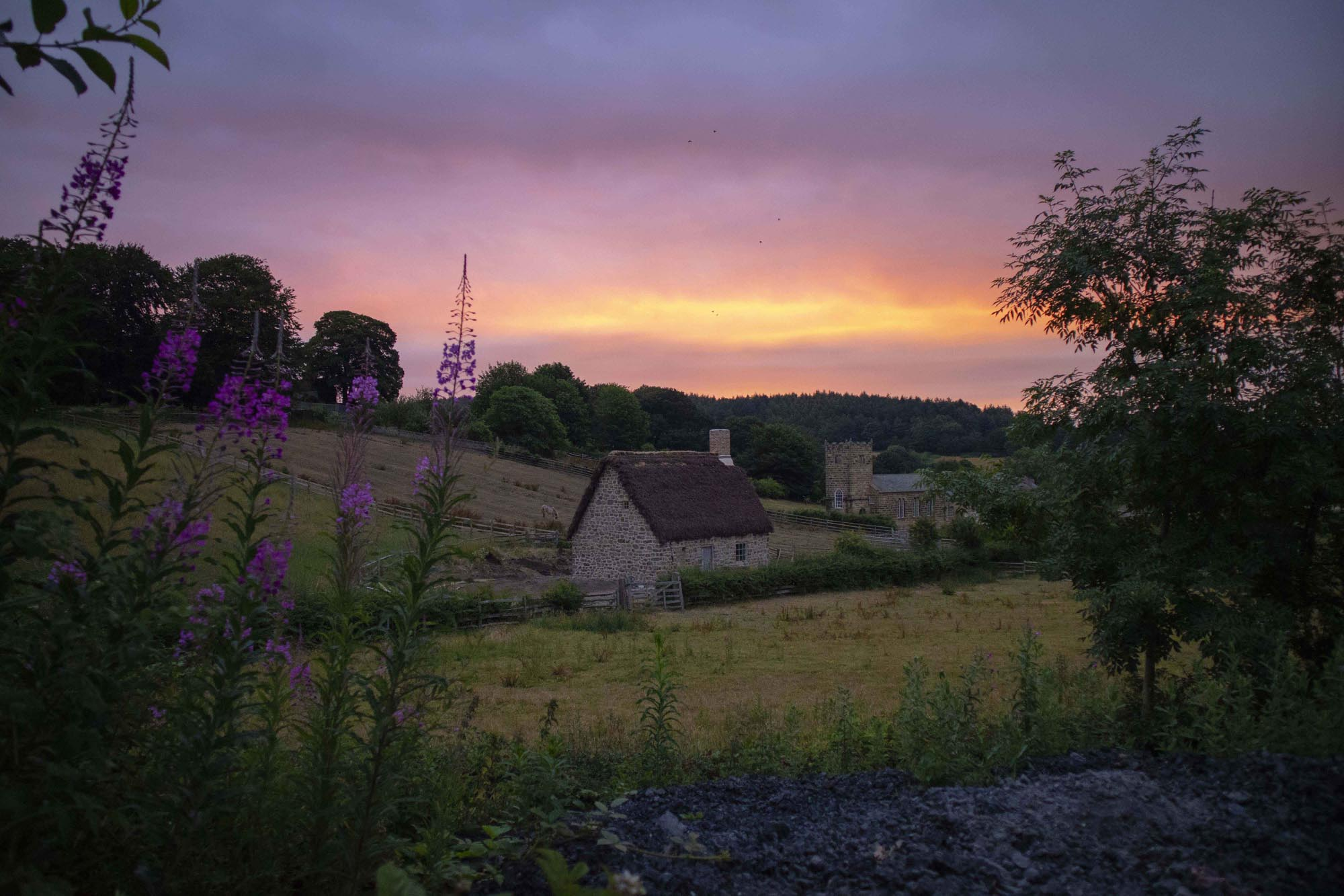 a photo of a stone cottage seen across fields with a summer red sunrise in the skies above
