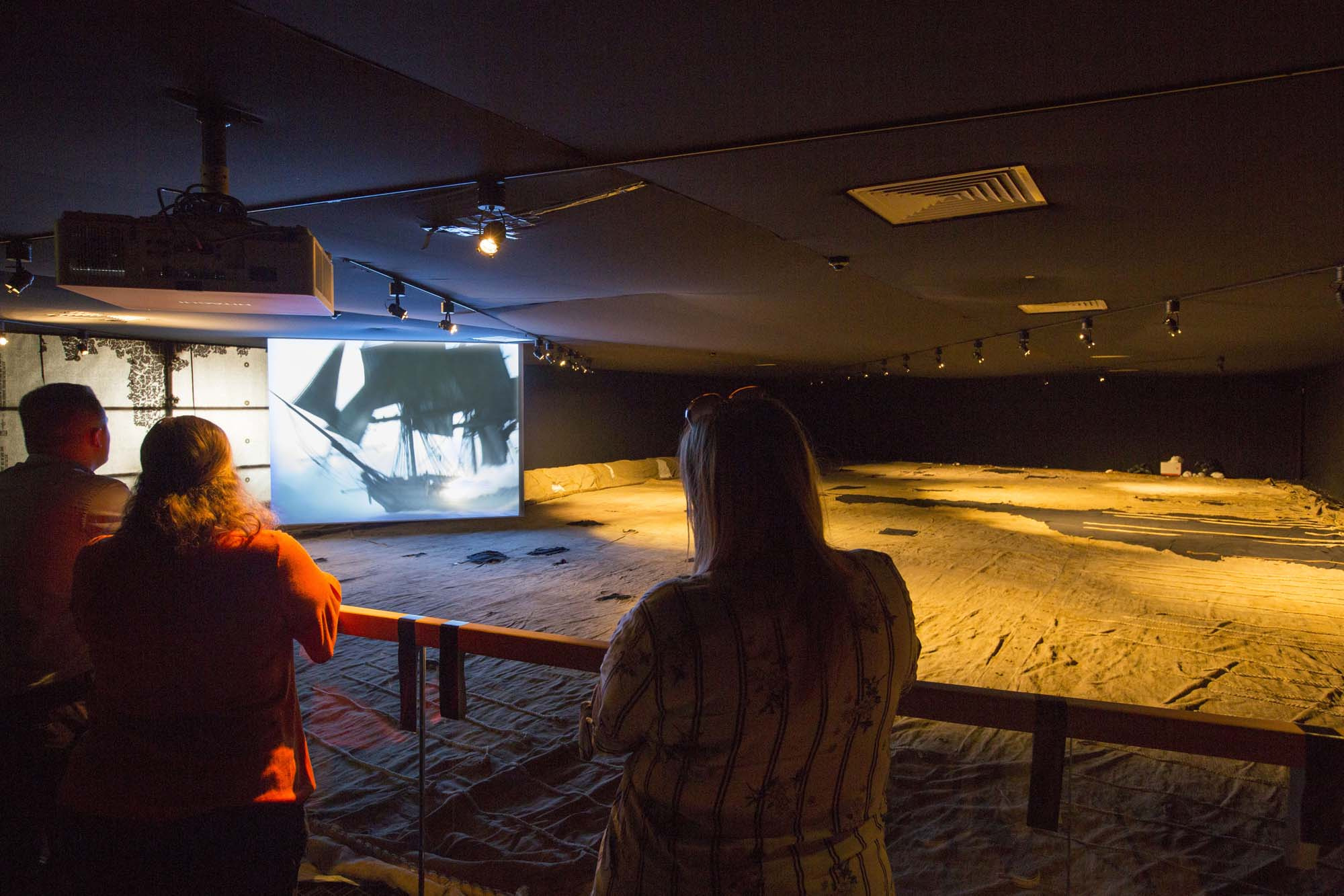 a photo of people looking across a room with a large sail laid out across it and a video screen showing films about sailing ships