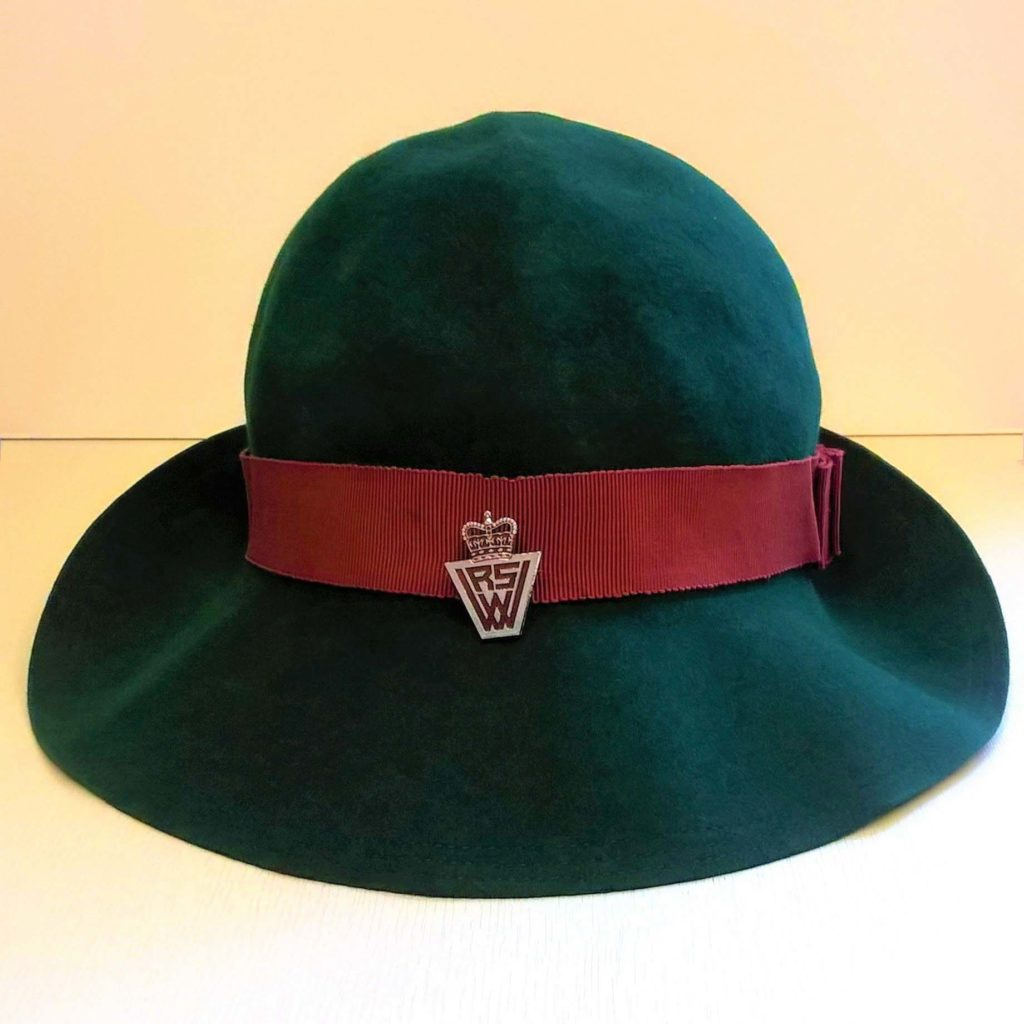 a photo of a hat with a large brim, red band and WRVS metal badge