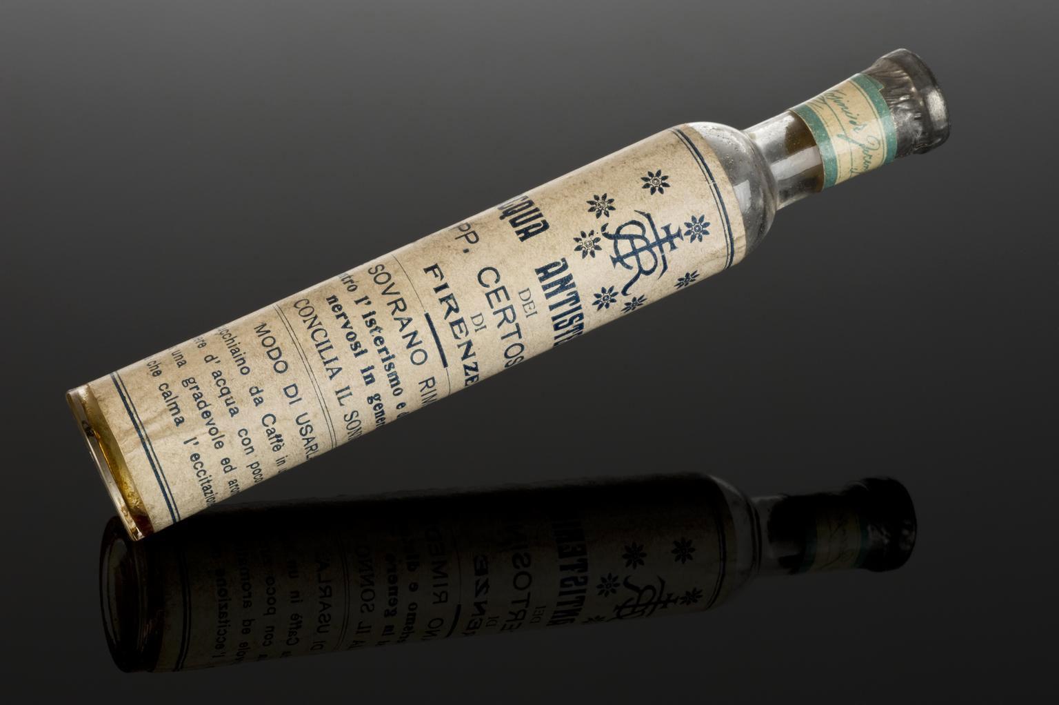 photograph of long thin bottle containing orange liquid, the bottle has a cream paper label