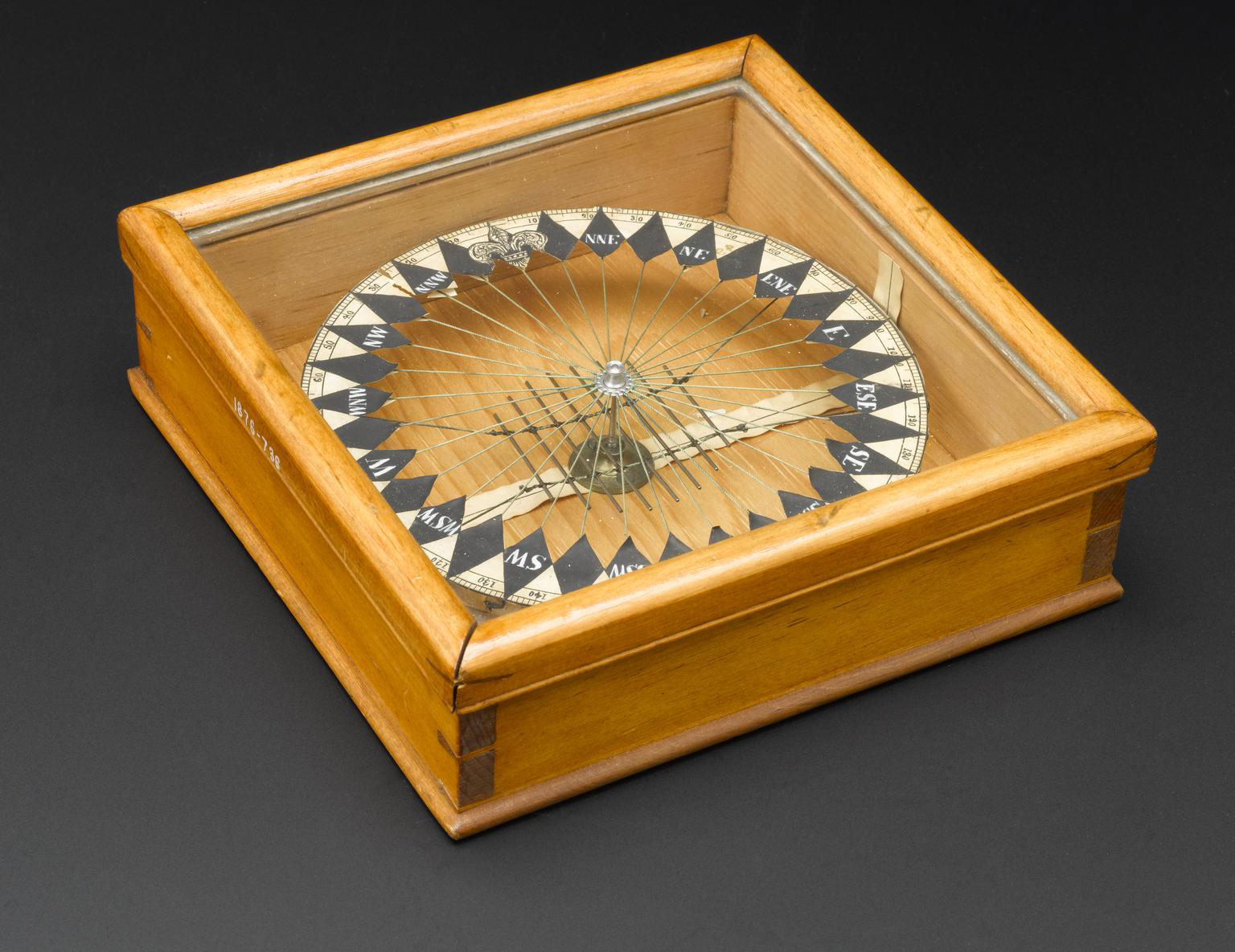 photograph of wooden box with glass lid containing compass-like instrument