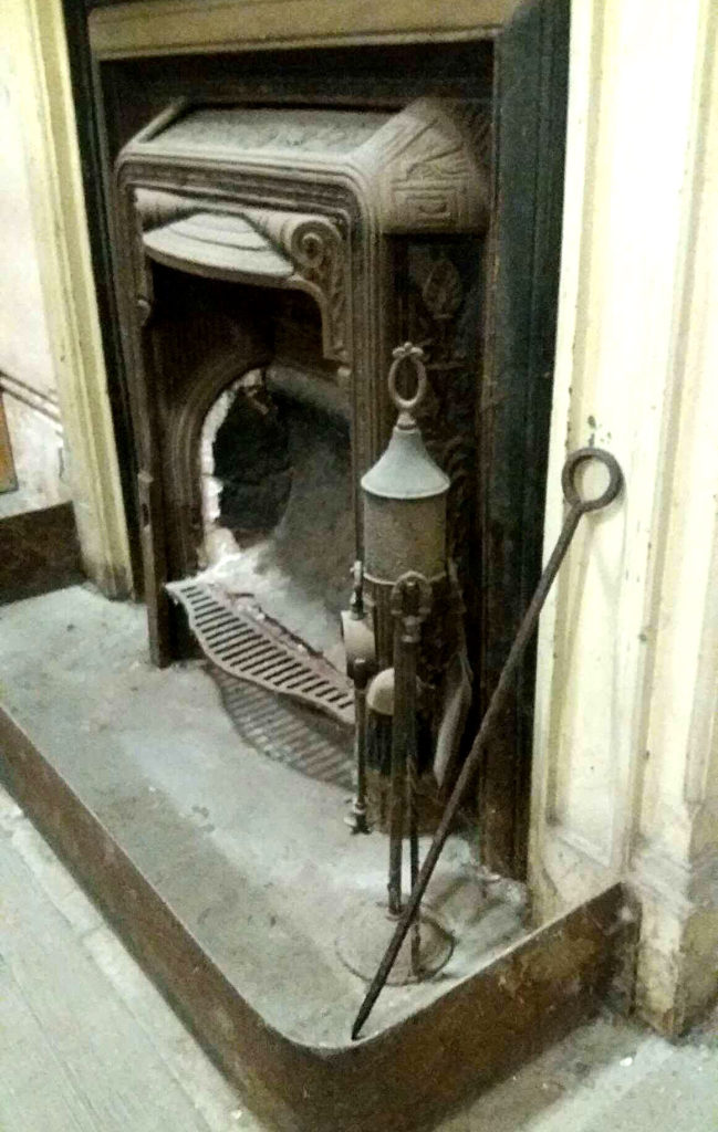 photograph of a fireplace with fireside tools