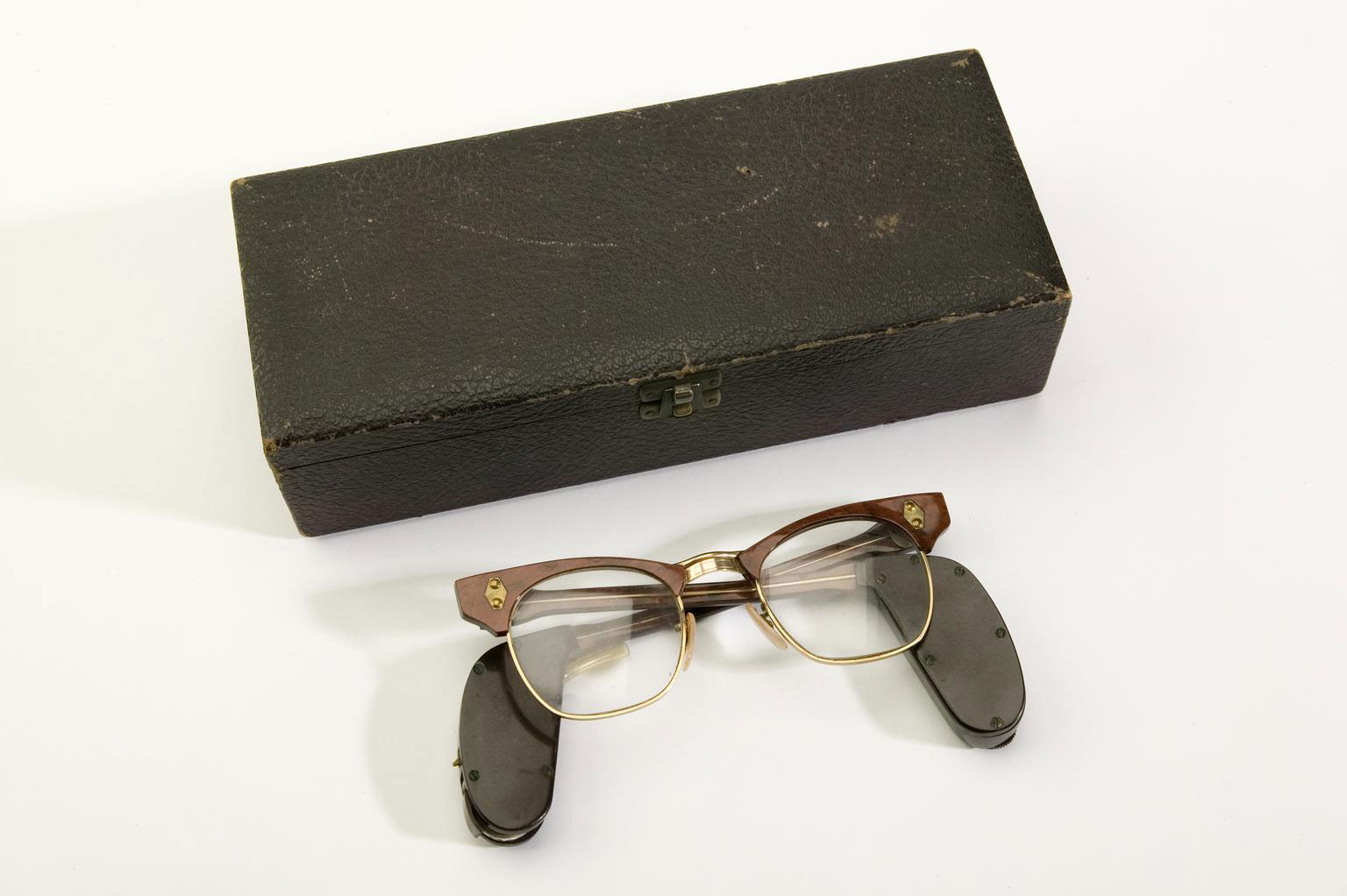 photograph of pair of spectacles with hearing aids attached to the arms next to a box