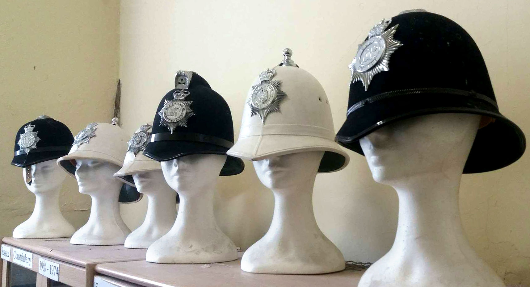photograph of six model busts wearing black and white police helmets
