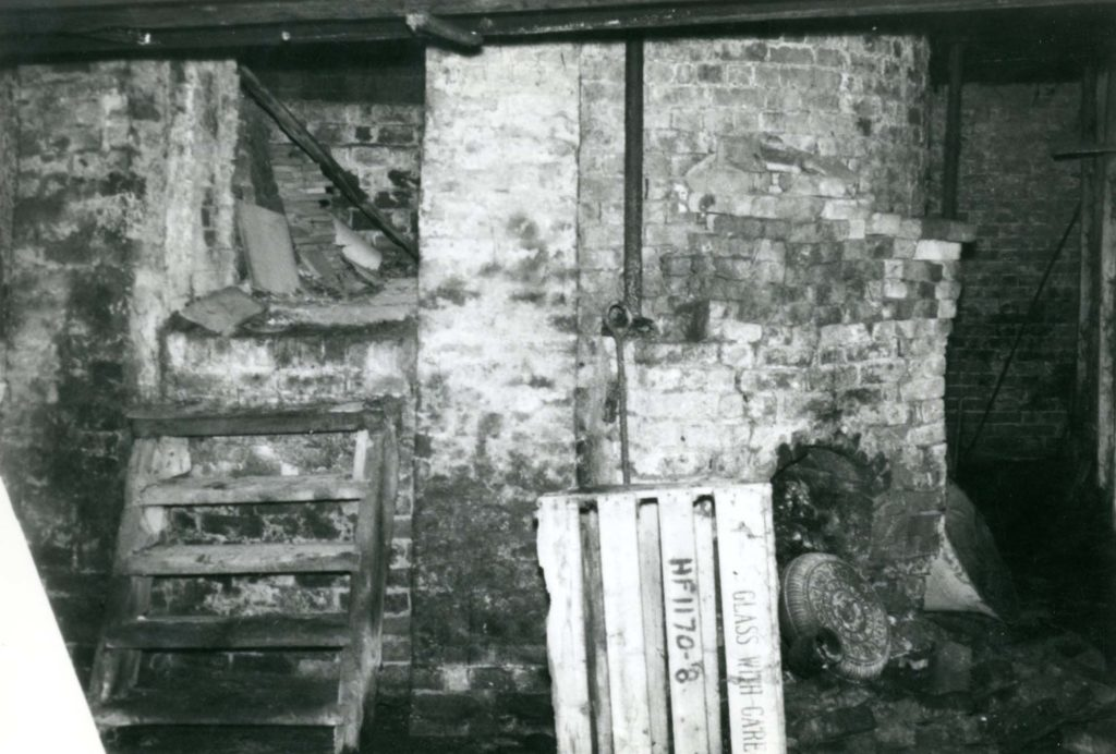 a photo of a brick kiln with wooden stairs leading up to a small compartment