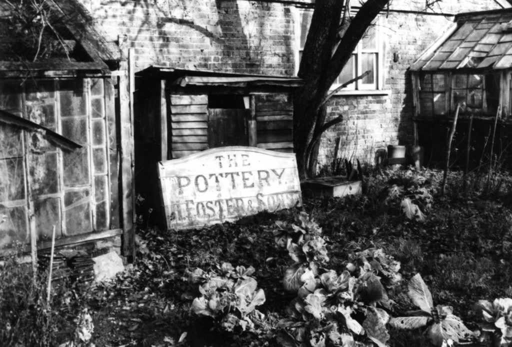 a black and white photo of an exterior of a building with a sign saying East Grinstead Pottery