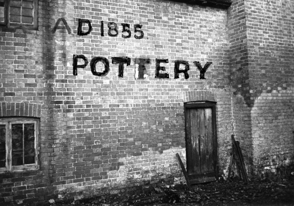 a photo showing the brick wallof a building with AD 1855 Pottery written onto the brickwork