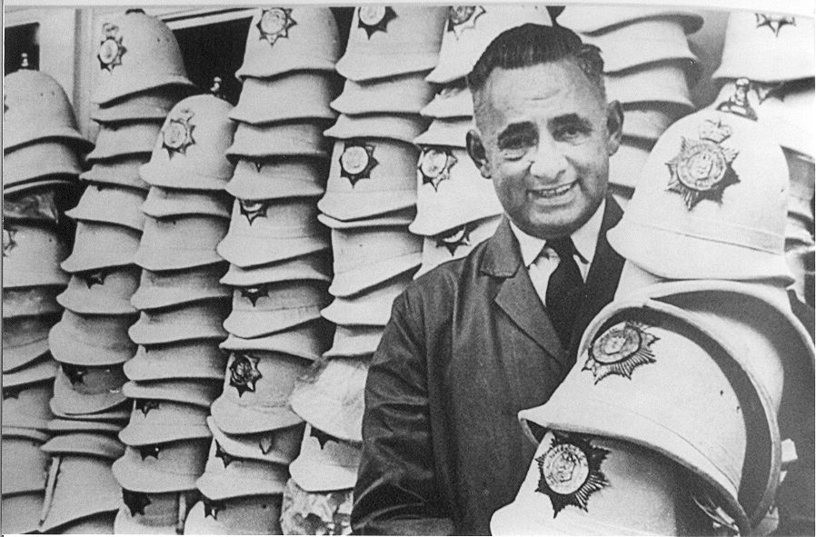 archive photograph showing man in front of stacks of white police helmets, holding sever helmets
