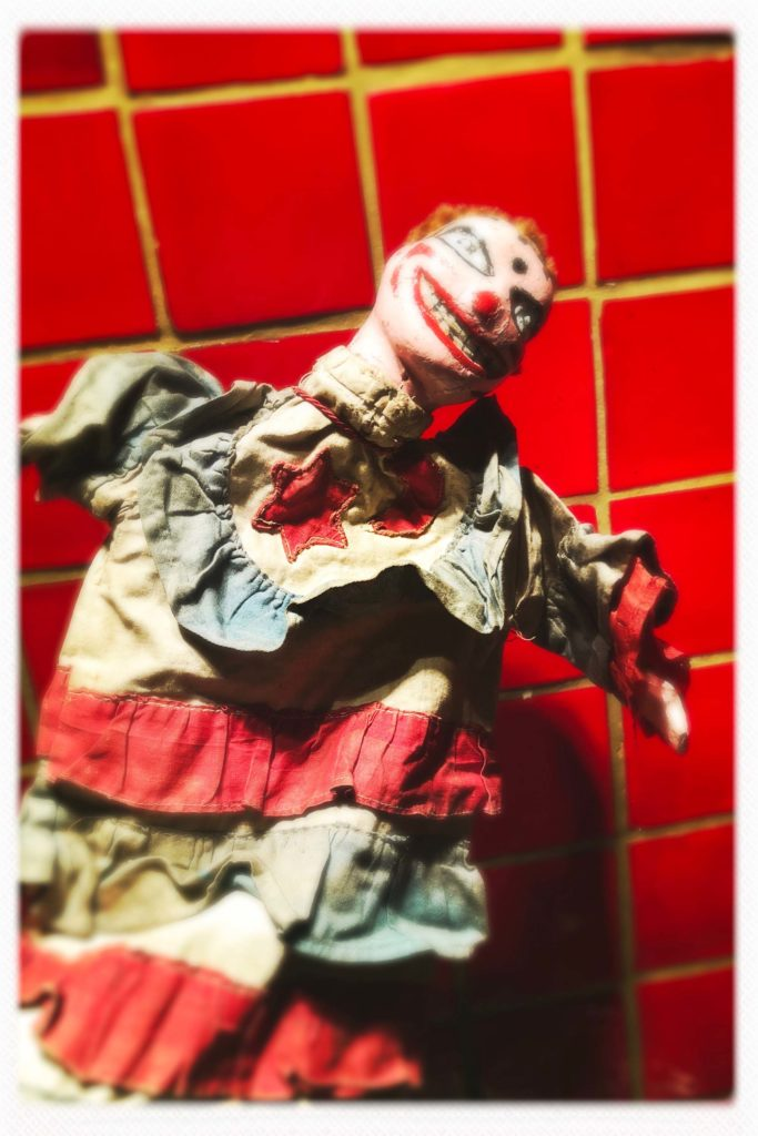 a photo of a wooden puppet character with dress and grotesque make up