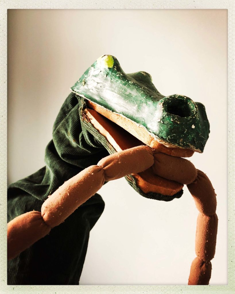 a photo of a crocodile puppet with a string of sausages in his mouth
