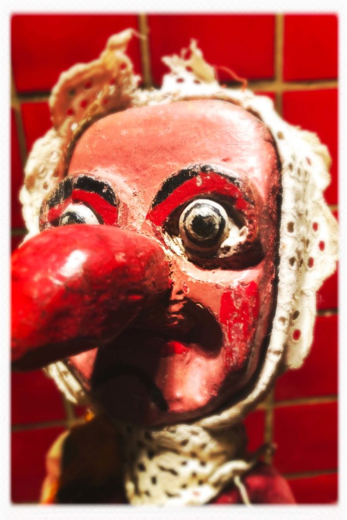 a photo of the wooden head of a Judy puppet with a large red nose
