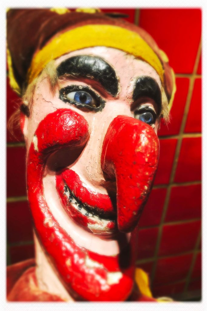 a photo of the wooden head of a punch puppet with red hooked nose and red cheeks