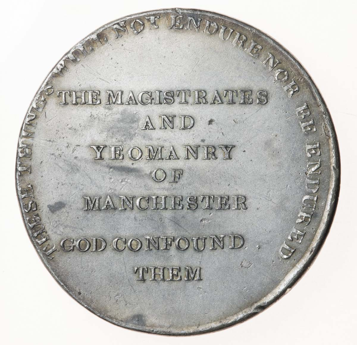 reverse of a silver medal with the words the magistrates and yeomanry of Manchester god confound them