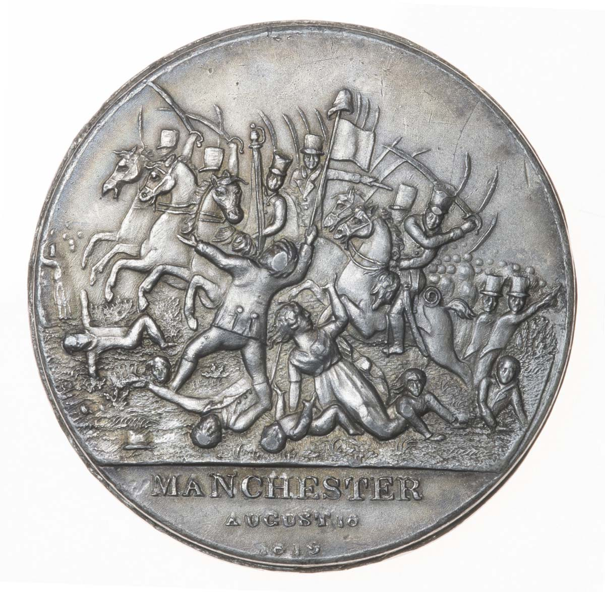 a photo of a round silver medallion with depiction of men on horseback cutting down women and children and the words Manchester August 16 1815