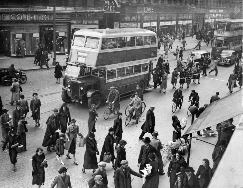 a black and white photo of a bus in crowded city streets with shop fronts and pedestrians, cars and cyclists milling around