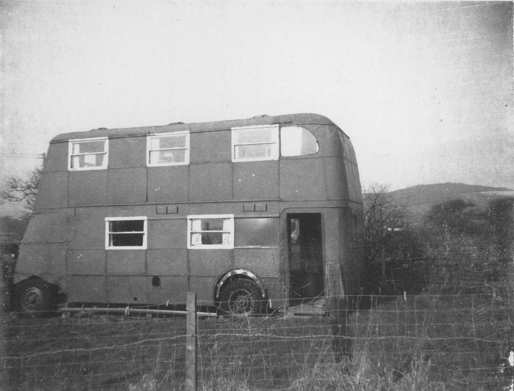 a black and white photo of an old double decker bus in a field