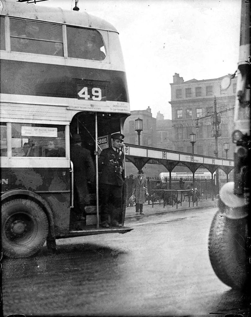 a black and white photo of a bus conductor perched on the back end of a double decker bus
