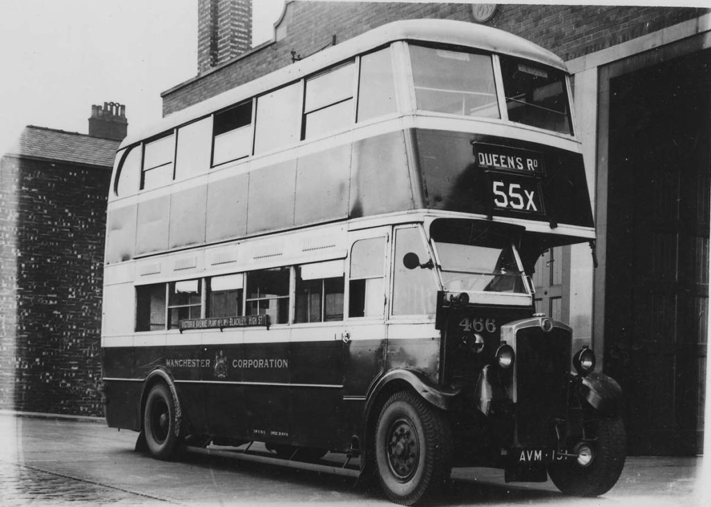 a black and white photo of an immaclate double decker bus parked outside a brick garage