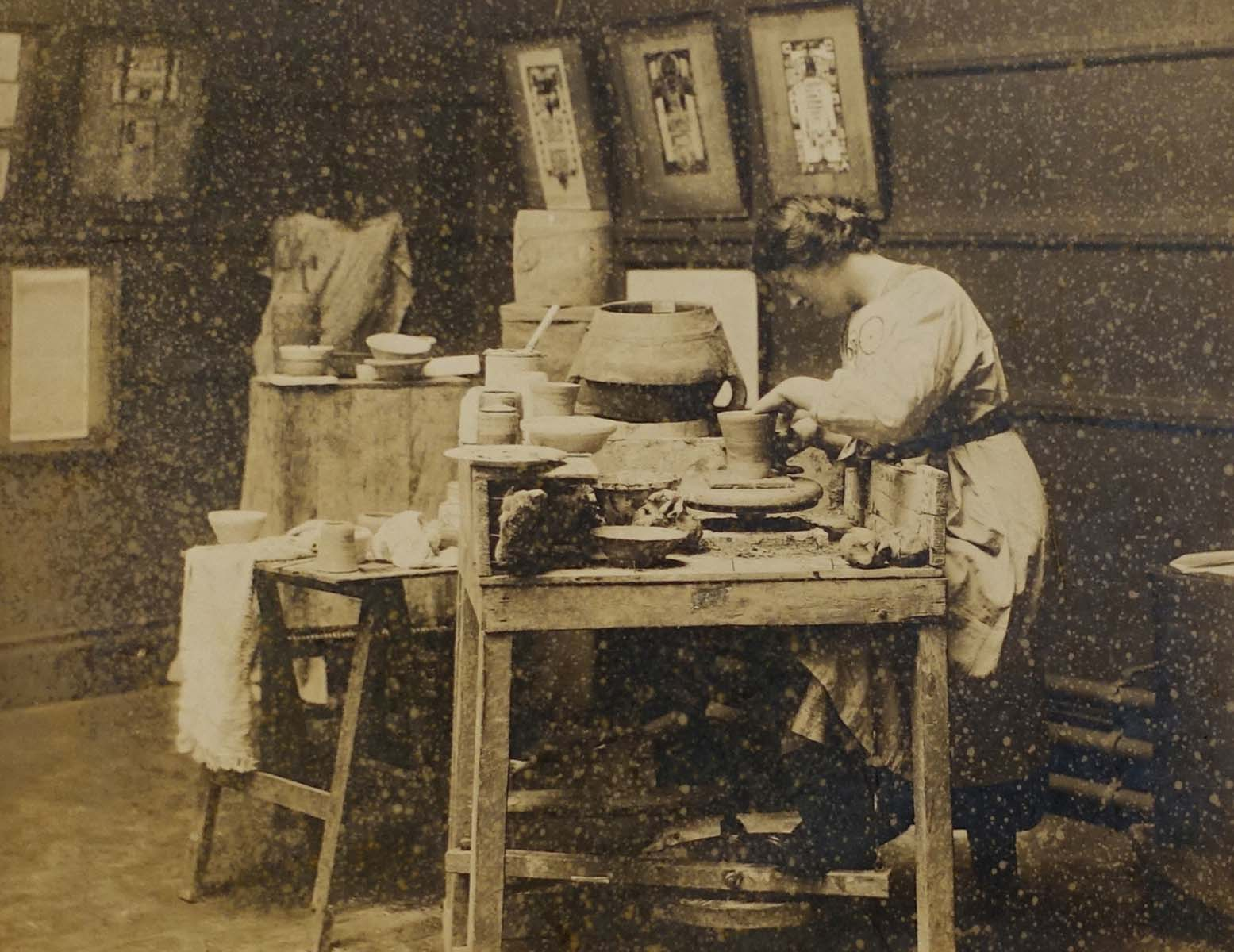 a sepia photo of a woman giving a pottery demonstration at a bench
