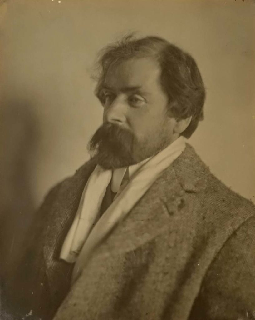 a sepia photo of a man with a rather fetching beard with walrus moustache wearing a tweed overcoat and silk scarf