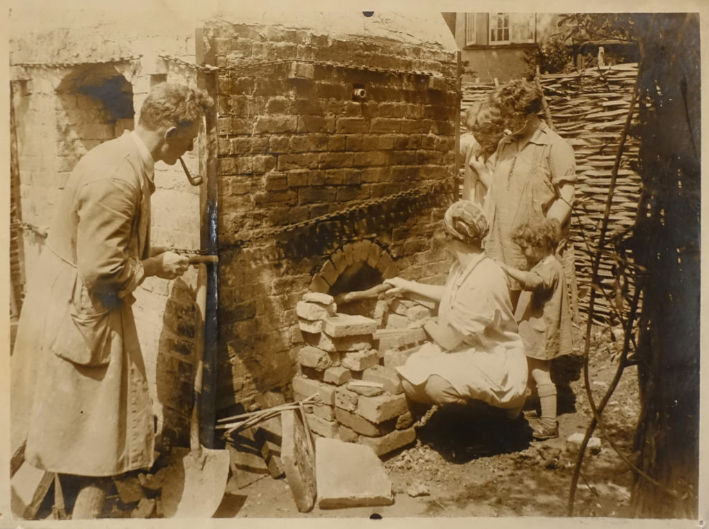 a black and white sepia toned photograph of a group of people looking at a kiln