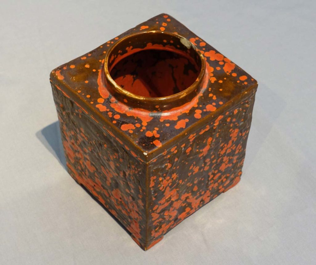 a square ceramic jug with circular neck and mottled orange and brown glaze