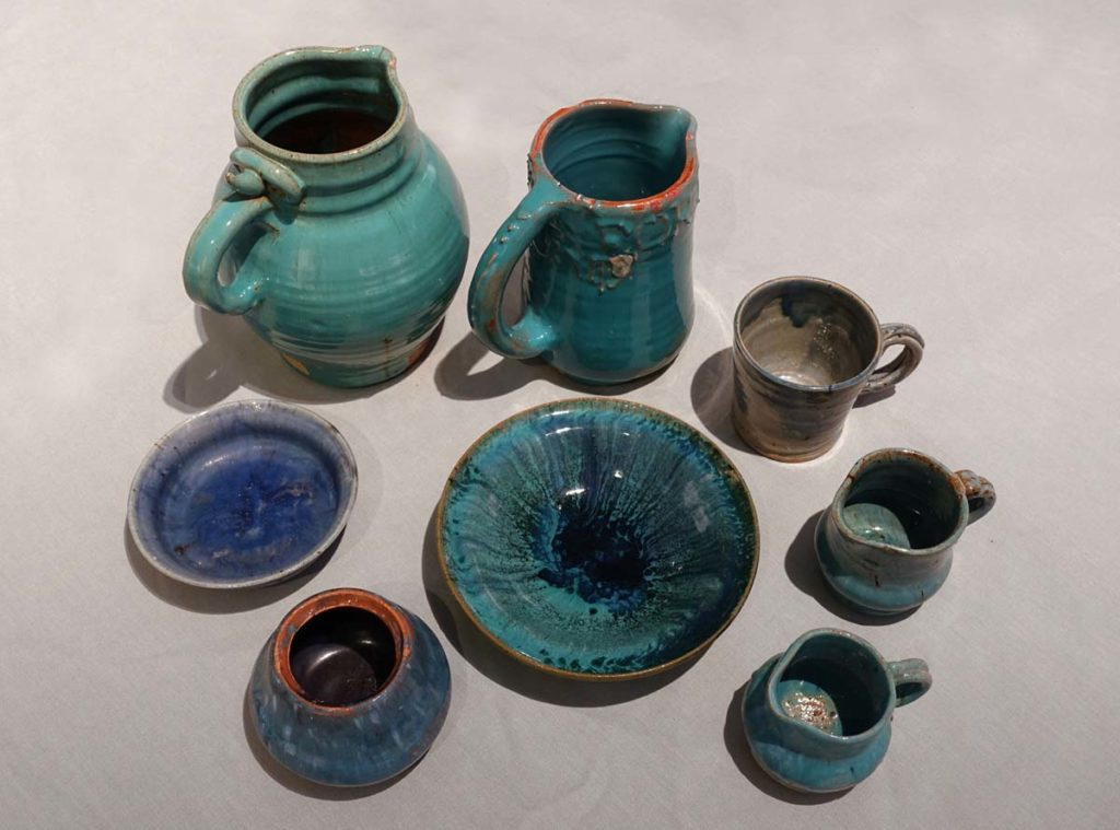 a selection of blue handled jugs and bowls in turquoise and blue-green glazes