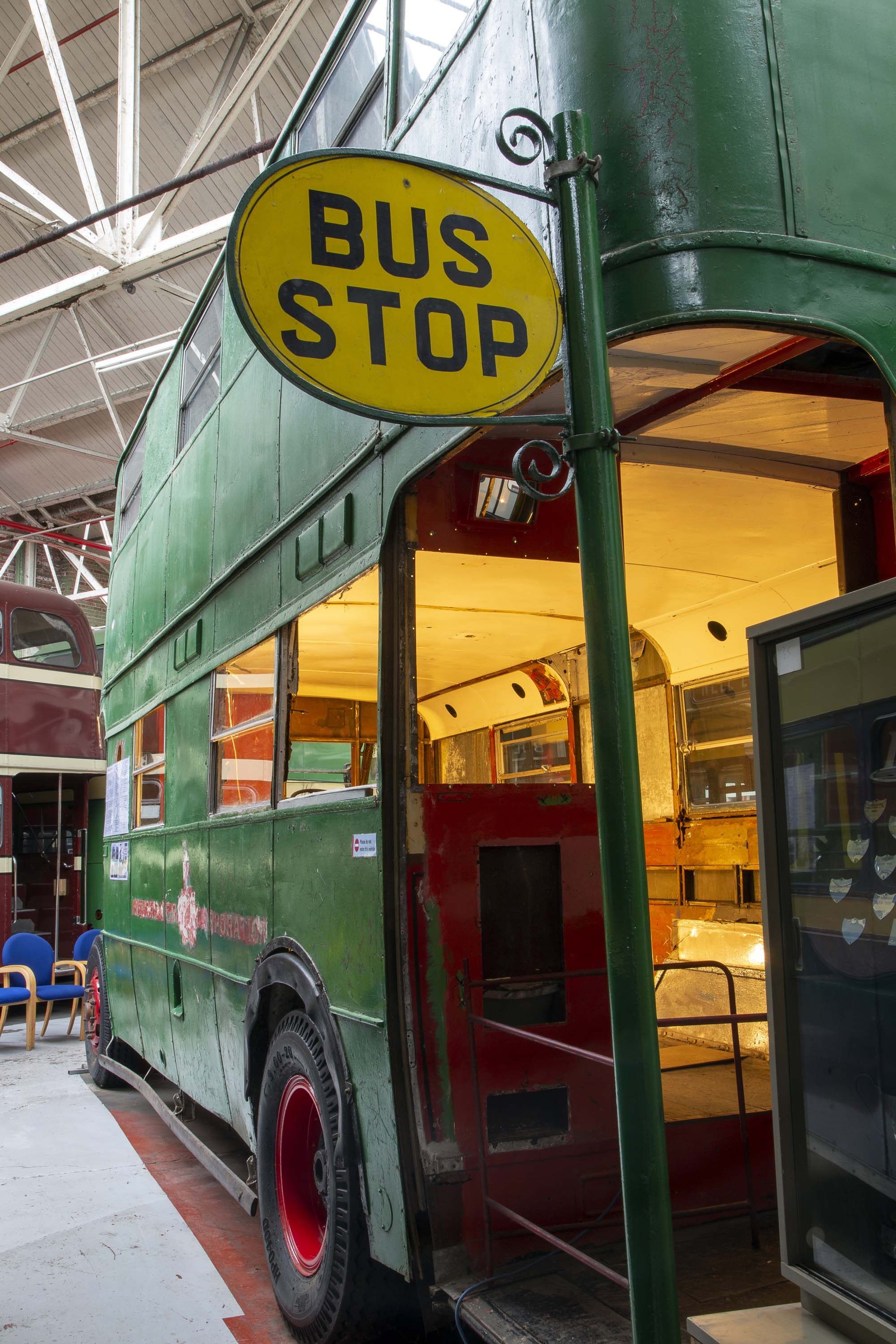 a photo of a dounel decker bus parked in a large warehouse seen from the back entrance