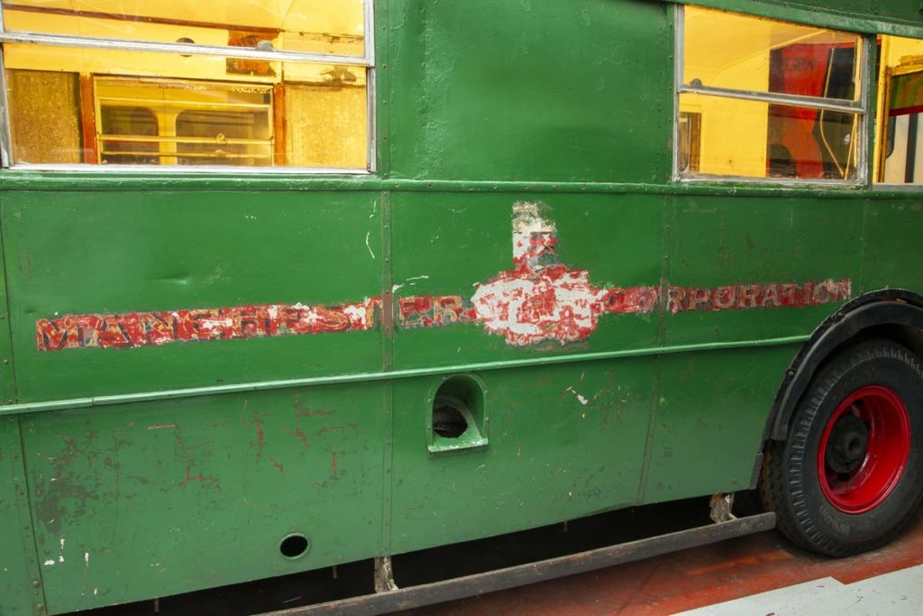 a photo of the side of a green double decker bus with a faded logo beneath layers of paint
