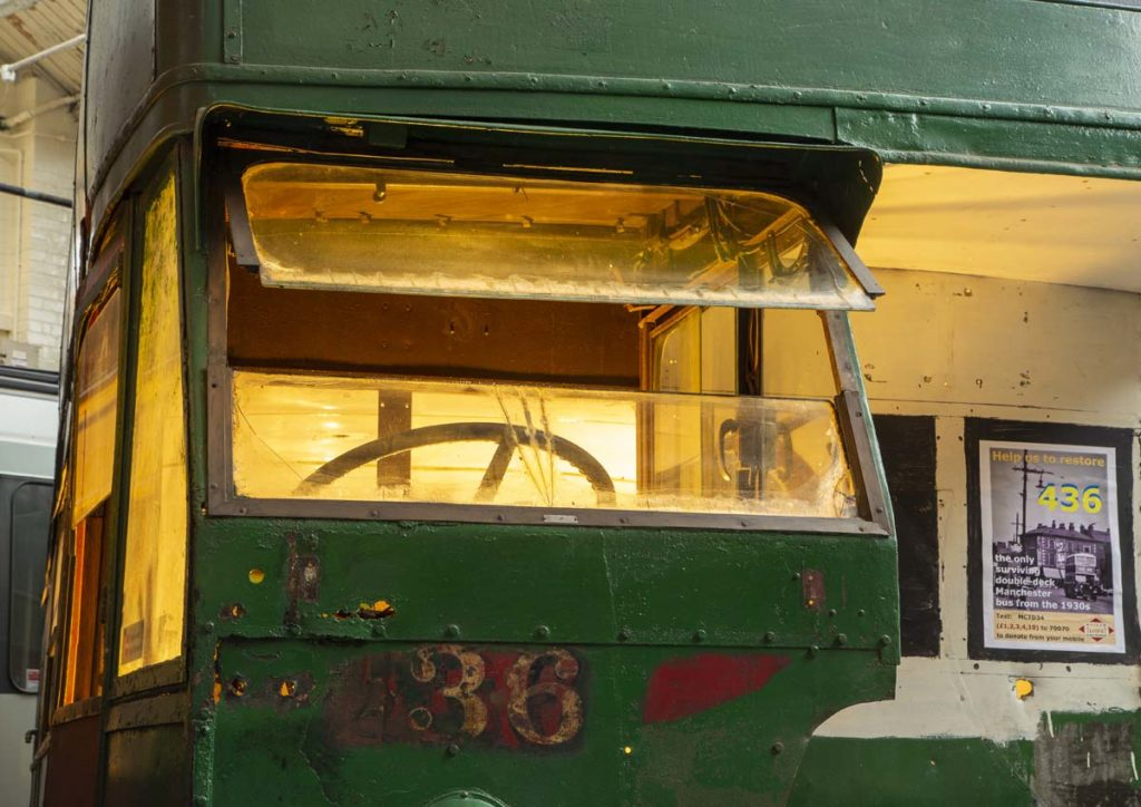 a photo of the cab of a double decker bus with the window open