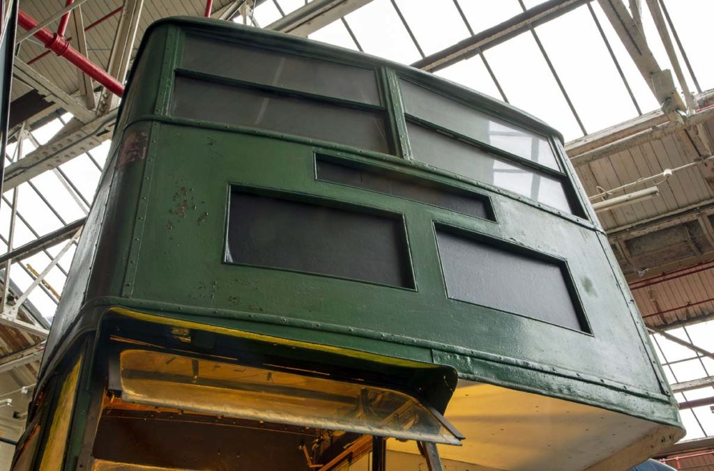 a photo of the front exterior of a double decker bus looking up into the front top deck