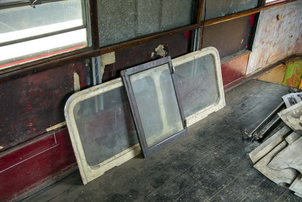 a photo of a pair of bus window frames resting inside the upper deck of a double decker bus