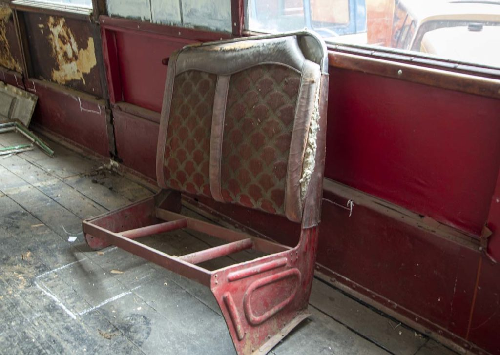 a photo of an old bus seat resting inside an old bus interior
