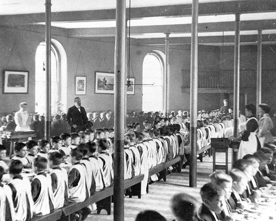 a black and white photo of kids in smock sitting in rows at bench tables
