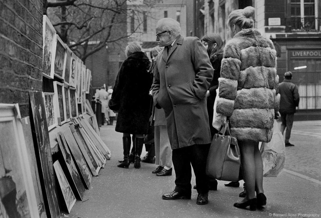 a black and white photo of people looking at artworks leaining against railingss