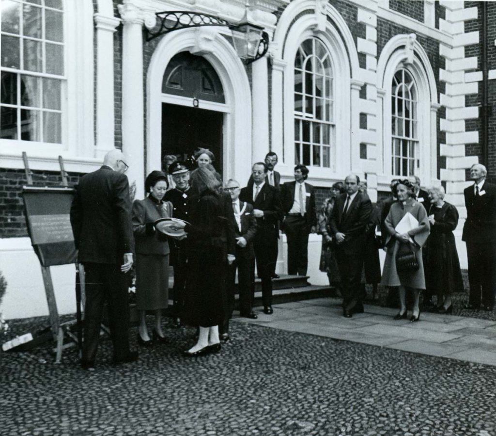 a black and white photo of dignitaries outisde a building