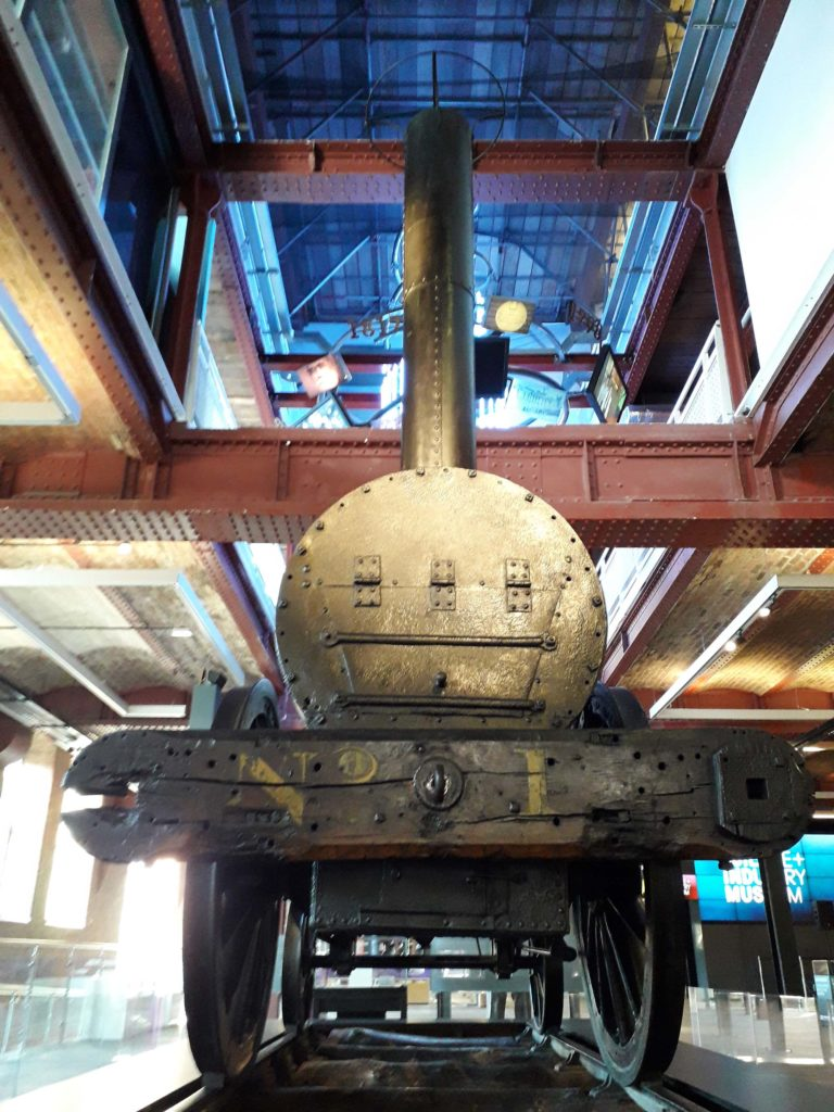 a frontal shot of the steam engine rocket in a museum display hall