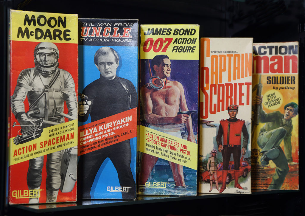 photograph of museum display showing several action figure boxes