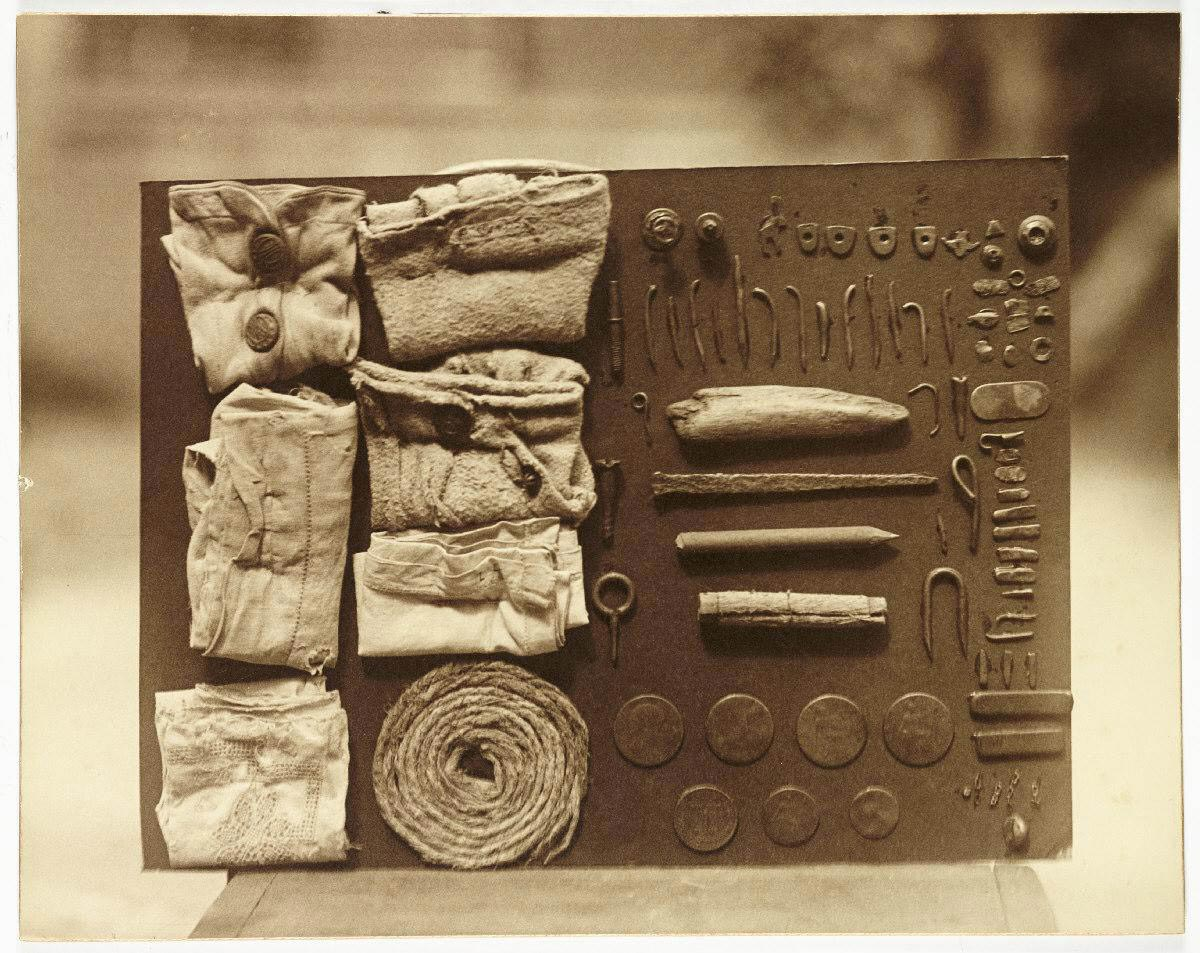 sepia toned photograph of board covered in objects including pieces of fabric, string, coins, hooks and buttons
