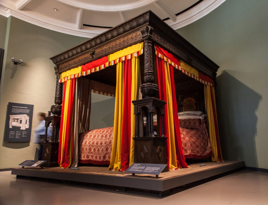 photograph of large four poster bed in dark wood with red and yellow drapes