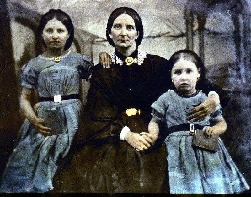 a colourised photo of a woman and her two young daughters in Victorian dress