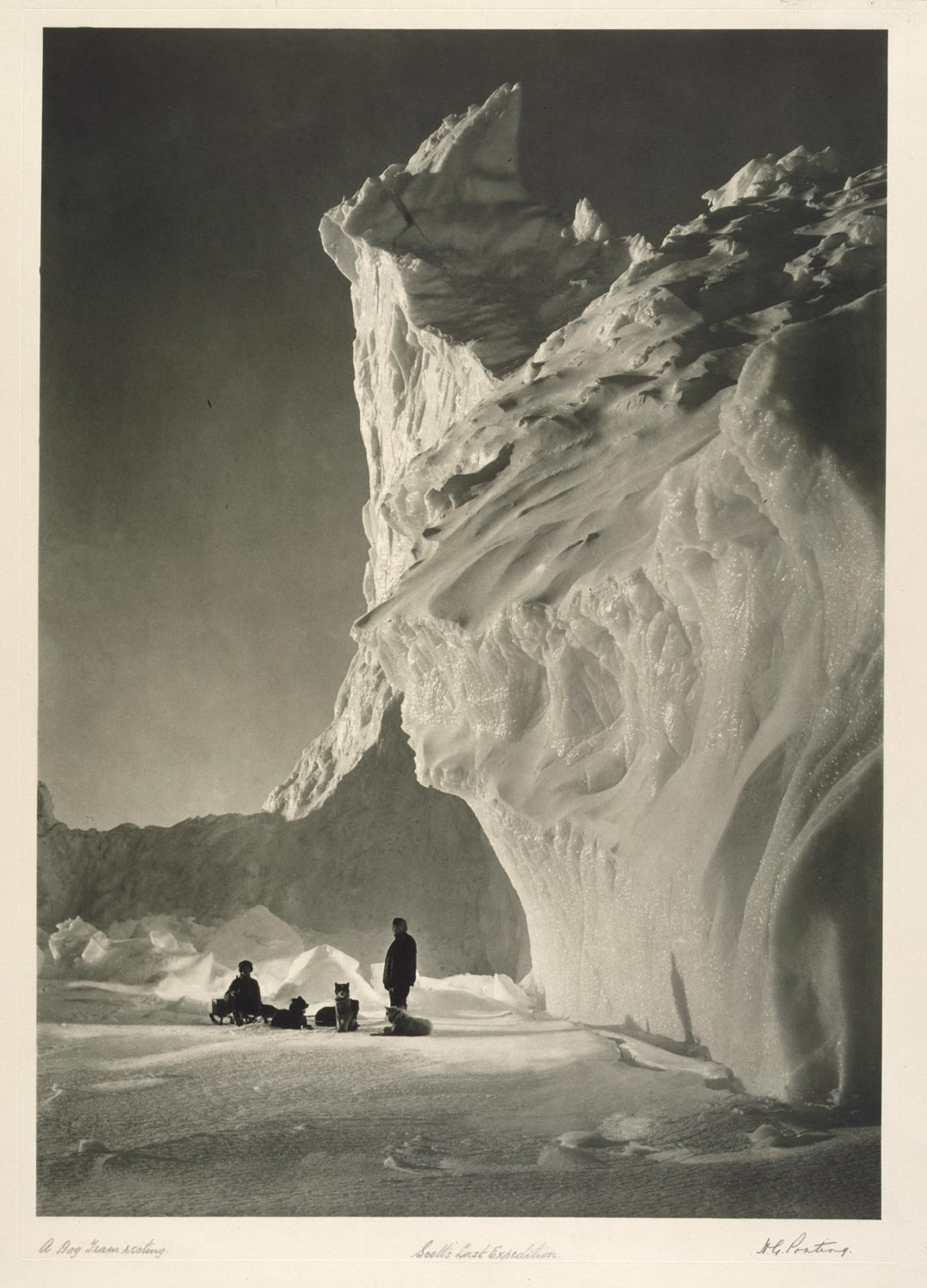 black and white photograph of large ice formation with two men and several dogs resting on the snow below