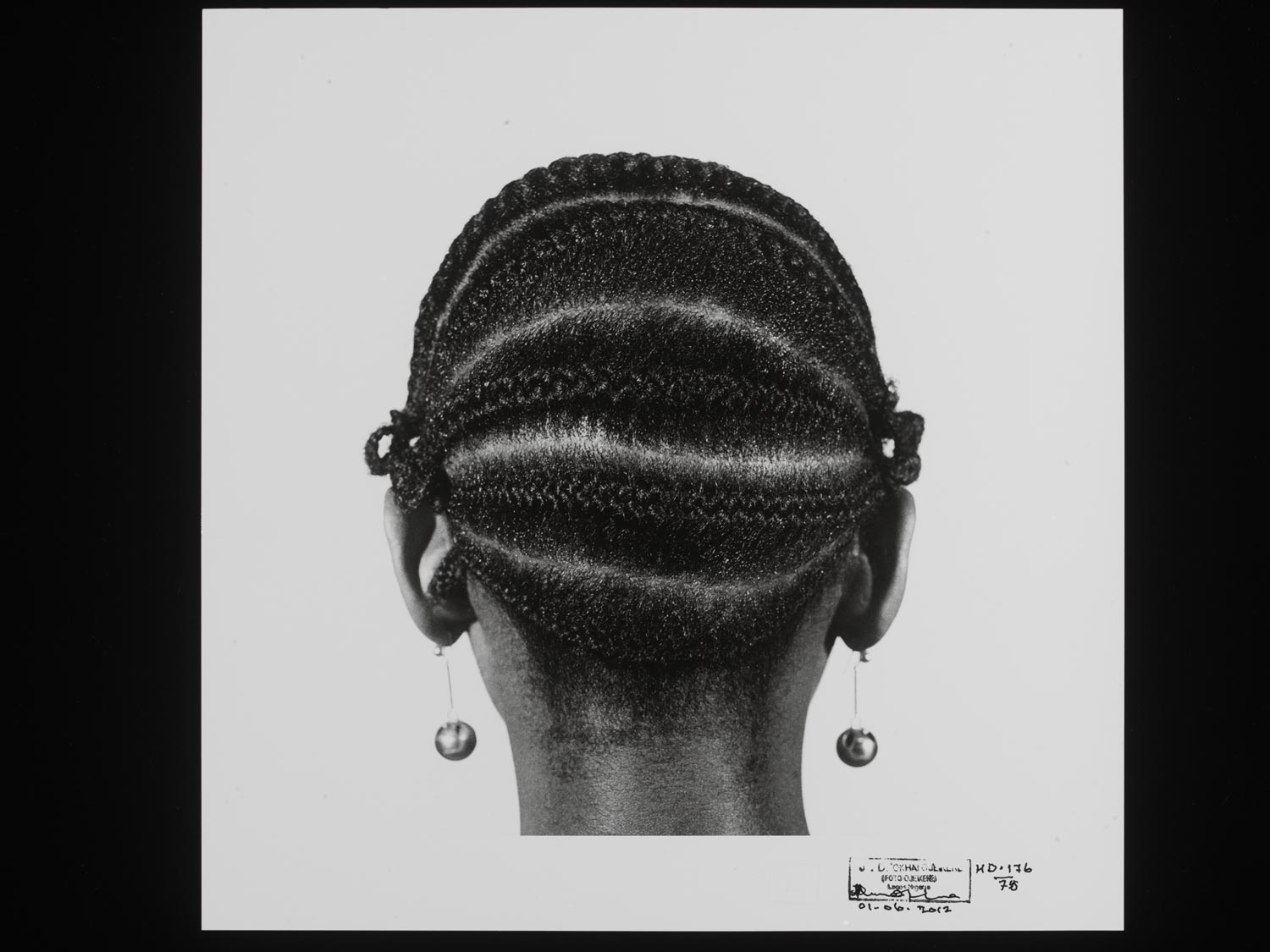 black and white photograph of the back of a woman's head with braids and hanging orb earrings
