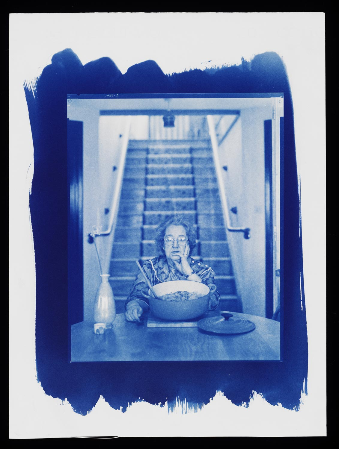 cyanotype image of old woman sat at a table with a large cooking dish