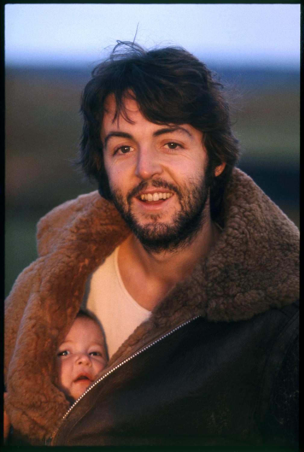 photograph of Paul McCartney wearing large shearling coat with baby inside
