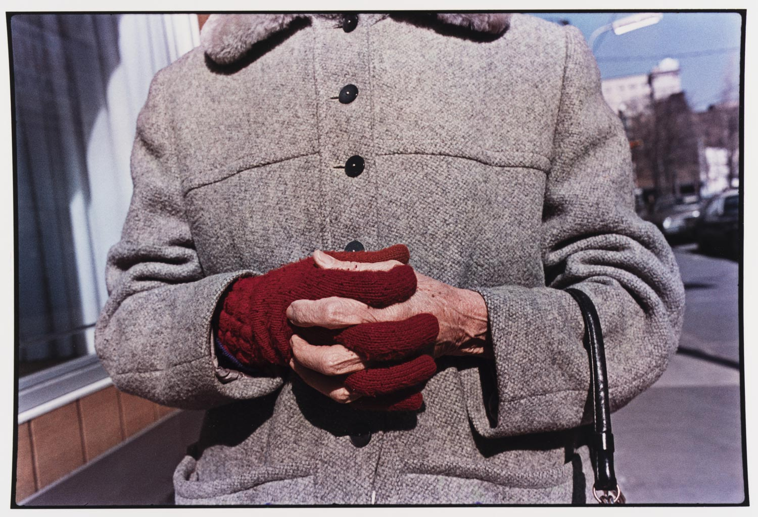 photograph of the torso of a person sstood on the street wearing a thick coat, they have one bare hand and are wearing a red glove on the other